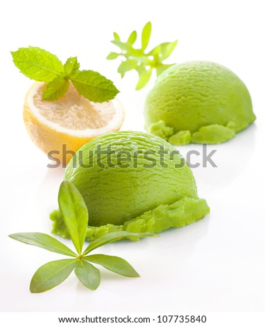 Scoops of fresh green lemon or lime icecream on a white studio background with faint reflection - stock photo