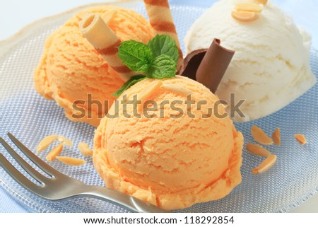 Scoops of ice cream garnished with wafer rolls