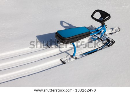 Scooter or snowmobile toy on winter snow hill - stock photo