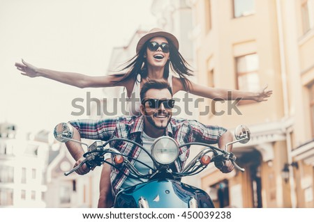Scooter ride. Beautiful young couple riding scooter together while happy woman keeping arms outstretched and smiling - stock photo