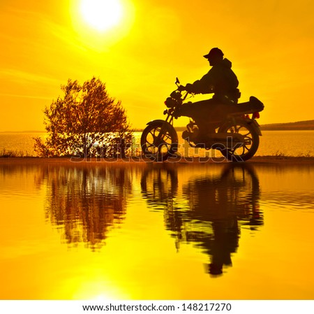 Scooter standing on a hill in the sunset With reflection on water Copy space for inscription  - stock photo