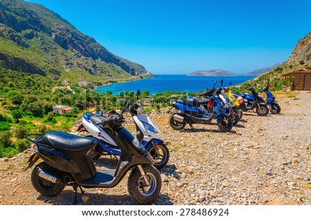 Scooters parked on parking with sea bay with beach behind, Greece - stock photo