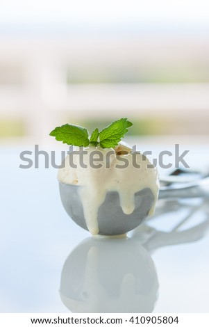 Scope of homemade vanilla ice cream in a metal spoon with fresh mint, closeup - stock photo