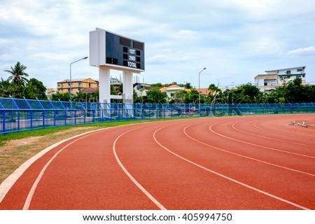 Scoreboard in local stadium and running track - stock photo