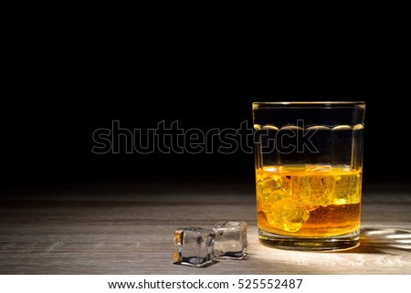 Scotch and light  on wooden background with copyspace. An old and vintage countertop with highlight and a glass of hard liquor.