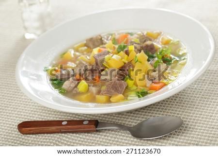 Scotch broth soup in a white bowl closeup - stock photo