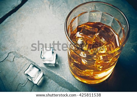 Scotch on rock background with copyspace. An old and vintage countertop with highlight and a glass of hard liquor  - stock photo