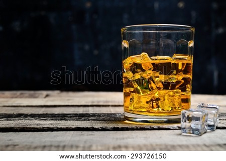 Scotch on wooden background with copyspace. An old and vintage countertop with highlight and a glass of hard liquor  - stock photo