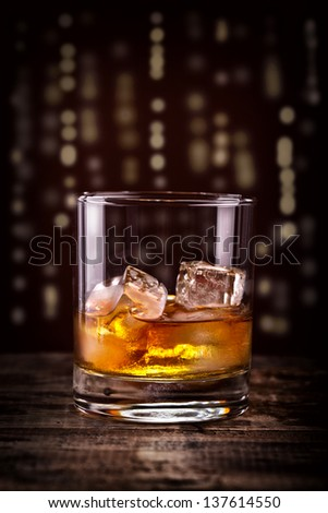 Scotch on wooden table with lightning skyline background, An old and vintage counter top with highlight and a glass of hard Liquor, Whisky or Whiskey and ice - stock photo