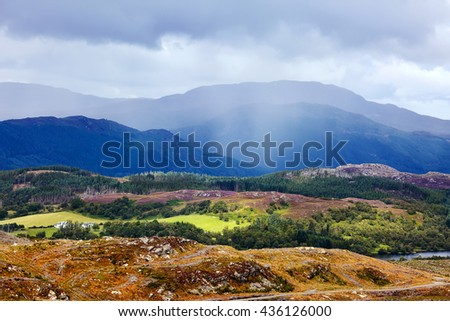 Scotland Landscape, dramatic rain clouds, with heather fields and mountains.  - stock photo