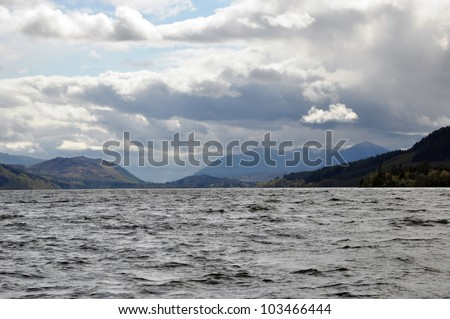 Scotland Loch Ness view. Water, mountains, black clouds and one little white cloud. - stock photo