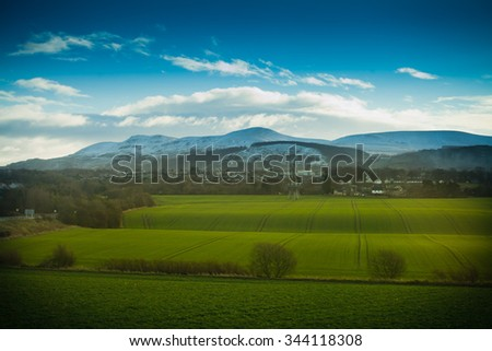 Scotland snow winter green fields - stock photo