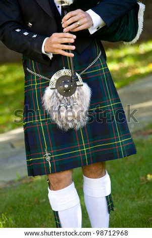 Scottish bagpiper playing bagpipes. This is a detail shot of a man wearing a kilt - stock photo