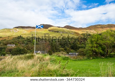 Scottish flag waving in a strong wind near Eilean Donan castle in Dornie, between Skye and the Highlands of Scotland. The sunny light baths the lush grass and forest under the clouds and mountains. - stock photo