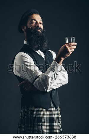 Scottish gentleman wearing a plaid kilt enjoying a glass of whiskey standing with crossed arms giving the camera a supercilious look - stock photo