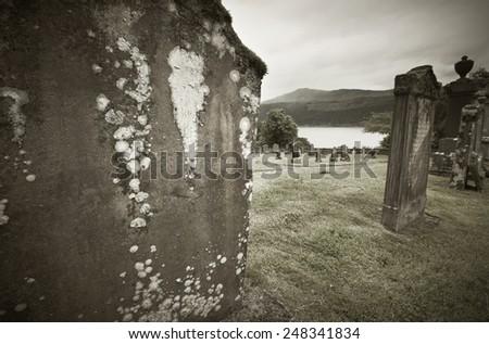 Scottish graveyard and Loch Ness in sepia tone. Horizontal - stock photo