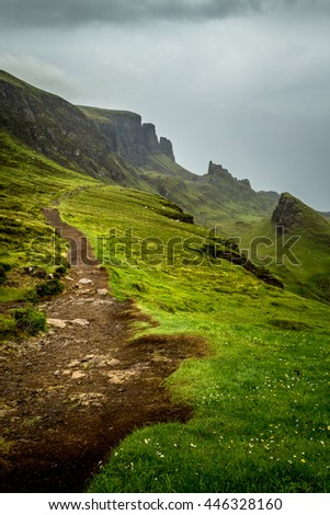 Scottish hiking path on the Quiraing, Isle of Skye, Scotland with lush and saturated green grass going from the foreground into the background hills and mountain peaks with overcast and cloudy sky