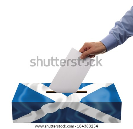 Scottish independence referendum ballot box covered in scotlands flag with person casting vote on blank voting slip - stock photo