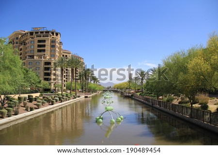 SCOTTSDALE, AZ - APRIL 11: The SRP canal in Oldtown Scottsdale on April 11, 2014 in Scottsdale, AZ. Oldtown Scottsdale is famous for its top-notch art scene, nightlife, and upscale shopping. - stock photo
