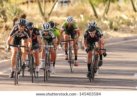 SCOTTSDALE, AZ - MAY 19: Cyclists compete in the Criterium at DC Ranch, a high-speed circuit race on a 1-kilometer closed course on May 19, 2013 in Scottsdale, AZ.  - stock photo