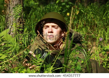 Scout in helmet and waterproof cape in summer forest