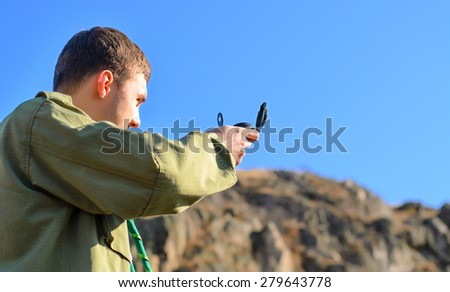 Scout taking a compass reading in the wilderness to pinpoint his location amongst the mountain peaks sighting along the pin