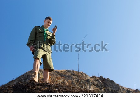 Scout using a magnetic compass to navigate as he explores the mountain wilderness standing on a cliff taking a reading of magnetic north, against a blue sky - stock photo