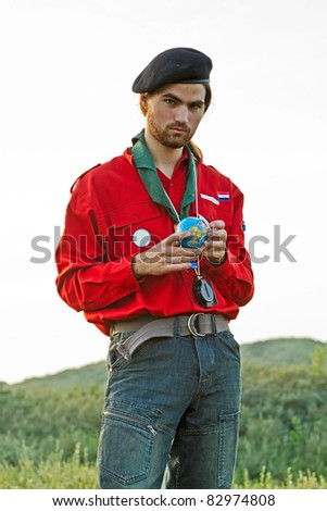Scout young man with little globe in his hands standing in grassy dune landscape. - stock photo