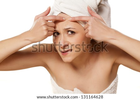 Scowling girl squeezes her acne with a towel on her head - stock photo