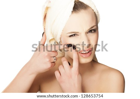 Scowling pretty girl squeezes her acne on her face - stock photo
