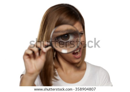 scowling young woman looking through a magnifying glass