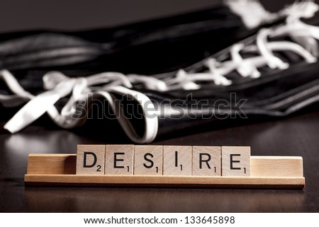 scrabble letters spelling the word desire with a corset in the background - stock photo