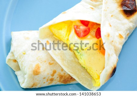 scrambled egg breakfast burrito with tomatoes and green onion and cheese