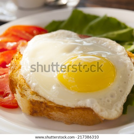 Scrambled egg on toast with tomatoes on plate - stock photo