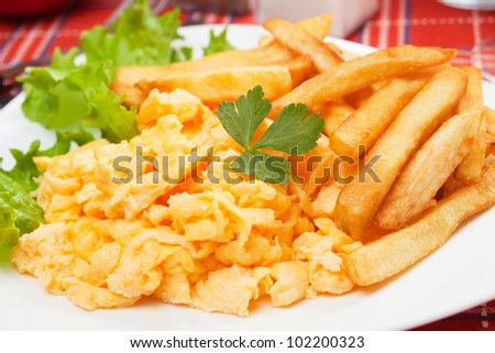 Scrambled egg with french fries and lettuce
