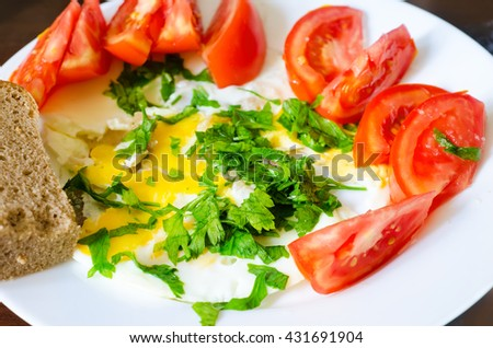 scrambled egg with tomato, parsley and bread