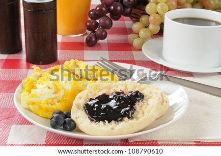 Scrambled eggs and an english muffin with blueberry jam - stock photo