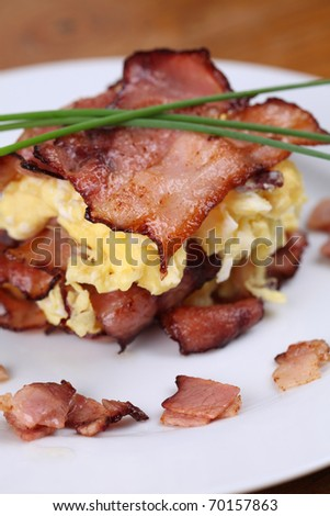 Scrambled eggs and bacon, garnished with chives on white plate