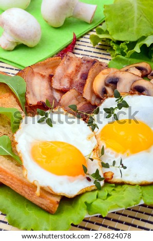 Scrambled eggs and bacon with croutons and salad leaves on plate - stock photo