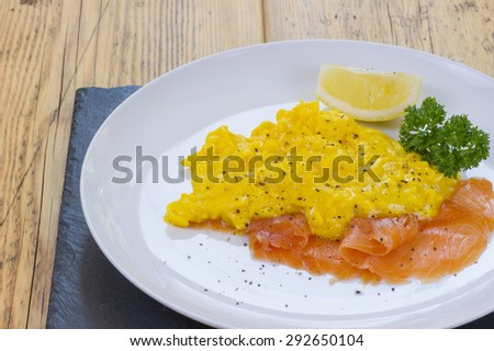 Scrambled eggs and salmon with lemon and parsley on the side