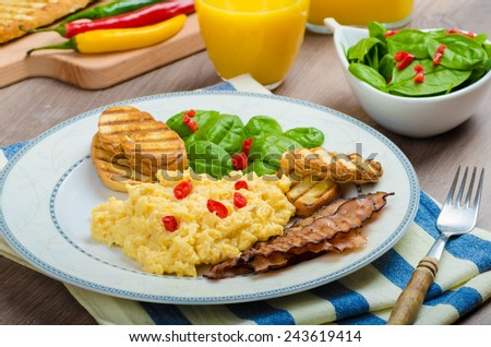 Scrambled eggs English style, bacon, fresh salad of spinach and microgreen, chilli pepper, orange juice