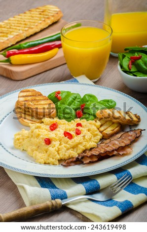 Scrambled eggs English style, bacon, fresh salad of spinach and microgreen, chilli pepper, orange juice - stock photo