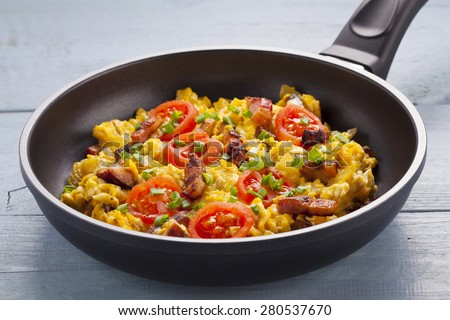 Scrambled eggs in a pan with bacon, onion and tomatoes sprinkled with chives, prepared from small farm eggs.