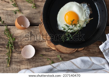 Scrambled eggs in an iron pan on the rustic wooden table - stock photo
