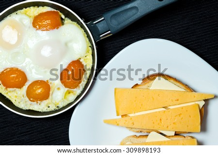 Scrambled eggs in the frying pan and sandwiches.