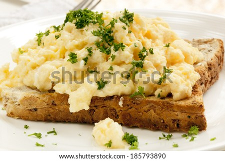 Scrambled eggs on toast, garnished with parsley. - stock photo