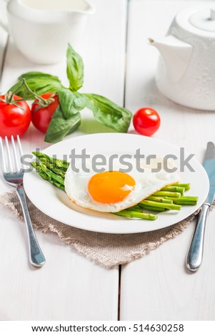 Scrambled eggs with asparagus served on white wooden background for breakfast