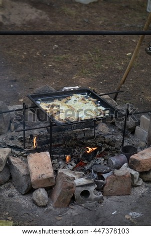 Scrambled eggs with bacon, meat, sausages, onions and eggs, fried in a pan on a fire in the forest