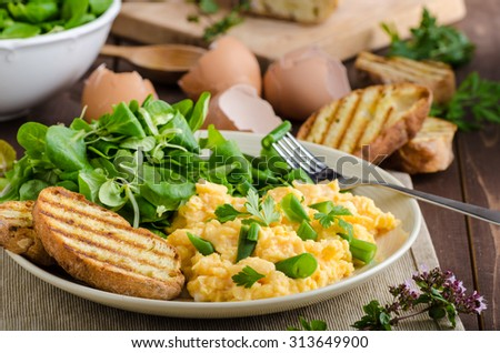 Scrambled eggs with beans and salad, baked baguette on a panini - stock photo