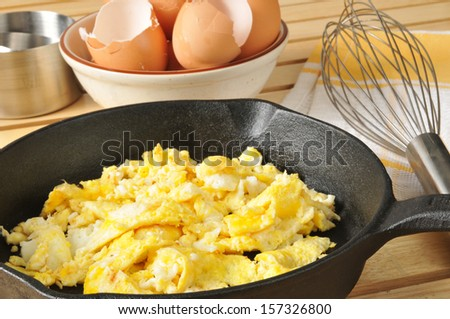 Scrambled eggs with brown egg shells in a bowl behind - stock photo